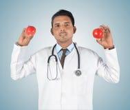 Jonge mannelijke arts die een rode appel houden Stock Foto's