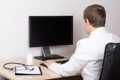 Jonge mannelijke arts die met computer in bureau werken Royalty-vrije Stock Afbeeldingen