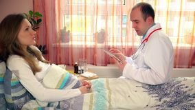 Jonge mannelijke arts die tabletcomputer met behulp van om verslagen over vrouwelijke patiënt te maken stock footage
