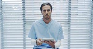 Jonge mannelijke arts gebruikend tablet en sprekend aan camera 4k stock videobeelden