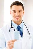 Jonge mannelijke arts met pak pillen stock afbeeldingen
