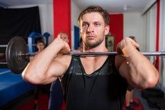 Jonge mannelijke atleet die barbell door boksring opheffen royalty-vrije stock foto