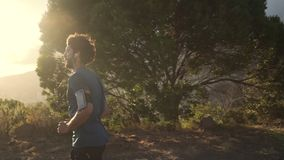 Jonge mannelijke atleet die bovenop heuvel lopen stock video