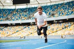 Jonge mannelijke atleet die op een renbaan lopen Stock Fotografie