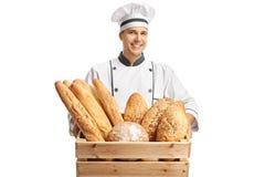 Jonge mannelijke bakker die een doos met verschillende types van brood houden stock afbeelding