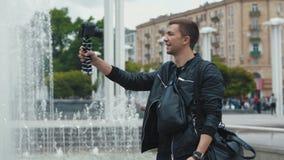 Jonge mannelijke blogger die videoblog van een stadsstraat uitzenden stock video