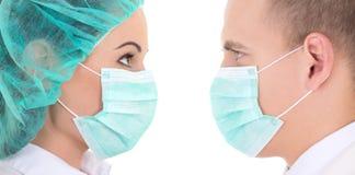 Jonge mannelijke en vrouwelijke chirurgen in beschermende die maskers op w worden geïsoleerd Stock Fotografie