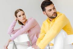 jonge mannelijke en vrouwelijke modellen in roze en gele hoodies die op stoelen zitten stock afbeeldingen
