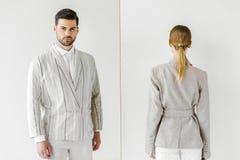 jonge mannelijke en vrouwelijke modellen in uitstekende kleren die en voorzijde bij camera achteruitgaan royalty-vrije stock fotografie