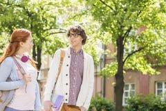 Jonge mannelijke en vrouwelijke studenten die terwijl het lopen op straat spreken Stock Fotografie