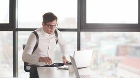 Jonge mannelijke financierzitting bij de documenten van de bureaulezing met geconcentreerde aandachtige uitdrukking stock videobeelden