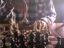 Jonge mannelijke grandmasterhand die volgende beweging het spelen schaak in donkere plaats op toernooien maken stock foto's