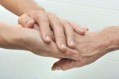 Jonge mannelijke hand die de hand van een oude vrouw houden royalty-vrije stock foto