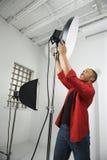 Jonge mannelijke het aanpassen studiolichten. Royalty-vrije Stock Afbeeldingen