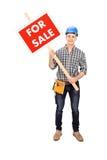 Jonge mannelijke ingenieur die a voor verkoopteken houden Royalty-vrije Stock Foto's