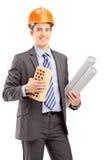 Jonge mannelijke ingenieur die een baksteen en een blauwdruk houden Stock Afbeelding