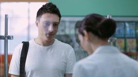 Jonge mannelijke klant het kopen geneeskunde bij apotheek stock footage