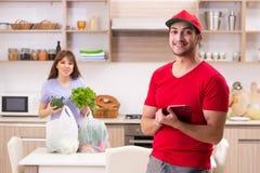 Jonge mannelijke koerier in het concept van de voedsellevering stock afbeelding