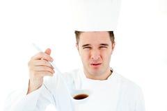 Jonge mannelijke kok die een slechte soep a proeft Royalty-vrije Stock Afbeelding