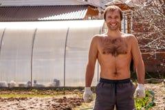 Jonge mannelijke landbouwer die gelukkig in de tuin glimlachen Stock Foto's
