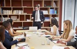 Jonge mannelijke manager die zich op een bedrijfsbestuurskamervergadering bevinden royalty-vrije stock afbeeldingen