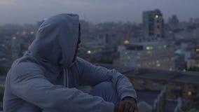 Jonge mannelijke misdadiger die voorzichtig die cityscape bekijken, in het leven wordt verward en wordt verloren stock videobeelden