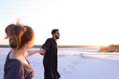 Jonge mannelijke Moslim leidt met de hand meisje en loopt langs woestijn bij s Royalty-vrije Stock Foto's