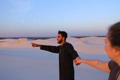 Jonge mannelijke Moslim leidt met de hand meisje en loopt langs woestijn bij s Royalty-vrije Stock Afbeeldingen