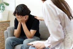 Jonge mannelijke patiënt die psycholoog raadplegen royalty-vrije stock foto