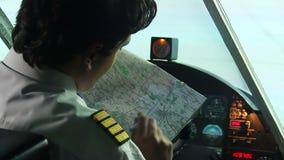 Jonge mannelijke proefzitting in cockpit, die plaats van aankomst op kaart merken, planning stock footage