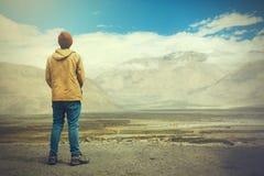 Jonge mannelijke reiziger die zich op de zandklip bevinden, denken over of zich op iets in Leh, Ladakh, India verheugen Royalty-vrije Stock Fotografie