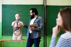 Jonge mannelijke Spaanse leraar in biologieklasse die, die digitale tablet houden en menselijk lichaamsanatomie onderwijzen, die  stock afbeeldingen