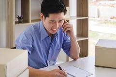 Jonge mannelijke start kleine bedrijfseigenaar die orde van klant ontvangen en door mobiele telefoon spreken stock afbeelding