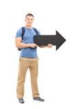 Jonge mannelijke student die een grote zwarte pijl houden Stock Foto's