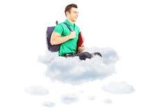Jonge mannelijke student met schooltaszitting op wolken en het kijken Stock Afbeelding