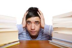 Jonge mannelijke studentenzitting die op bureau wordt gefrustreerd royalty-vrije stock foto