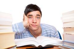 Jonge mannelijke studentenzitting met boeken op lijst stock foto's
