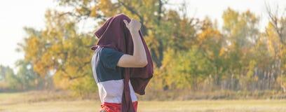 Jonge mannelijke tienerhipster gezet op een sweatshirtsweater die in openlucht op aardgebied F lopen stock afbeeldingen