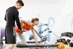 Jonge mannelijke trainer die instructies geven aan een vrouw in een gymnastiek Stock Foto's