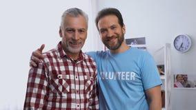 Jonge mannelijke vrijwilligers het koesteren hogere mannelijk en allebei die aan camera, liefdadigheid glimlachen stock video