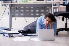 Jonge mannelijke werknemer ongelukkig met het bovenmatige werk stock afbeelding