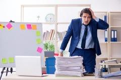 Jonge mannelijke werknemer ongelukkig met het bovenmatige werk royalty-vrije stock afbeeldingen