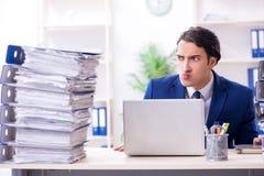 Jonge mannelijke werknemer ongelukkig met het bovenmatige werk royalty-vrije stock foto