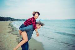 Jonge mannen die op de rug rit geven aan vrouwen op strand Jong paar die pret samen met blauwe oceaanachtergrond hebben Concept m Royalty-vrije Stock Foto