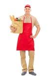 Jonge marktverkoper die een zakhoogtepunt van kruidenierswinkels houden Stock Afbeelding