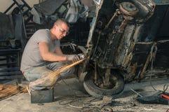 Jonge mechanische arbeider die een oude uitstekende auto herstellen stock fotografie