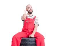 Jonge mechanische zitting op autowiel en het tonen als Stock Afbeeldingen