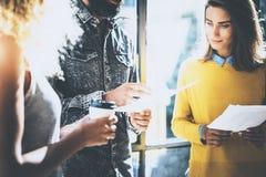 Jonge medewerkers die bedrijfsideeën in een bureau bespreken Man die het document houden zijn handen en met een vrouw spreken Stock Afbeeldingen