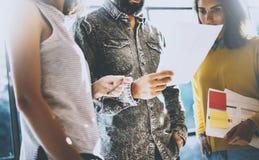 Jonge medewerkers die businessplannen in een bureau bespreken Mens die het document houden zijn handen en met collega's spreken Royalty-vrije Stock Afbeeldingen