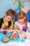 Jonge meisje en jongen die paaseieren schilderen Stock Foto's